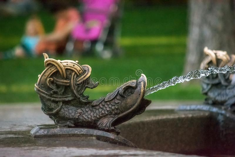 Kiev, Ukraine - 27 July 2019: Metal fish on the fountain near the pedestrian-bicycle bridge. Splashing water from the fish`s mout. H. Blurred background. Kyiv royalty free stock photos