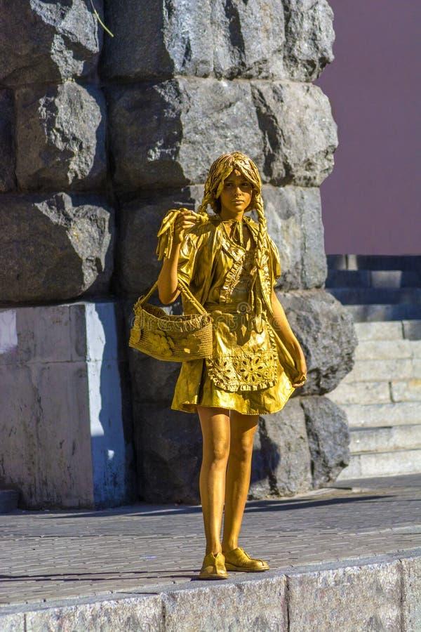Kiev, Ukraine, le 7 août 2018 Fille dépeignant une statue sur une rue de ville Une statue vivante peinte en or photos stock