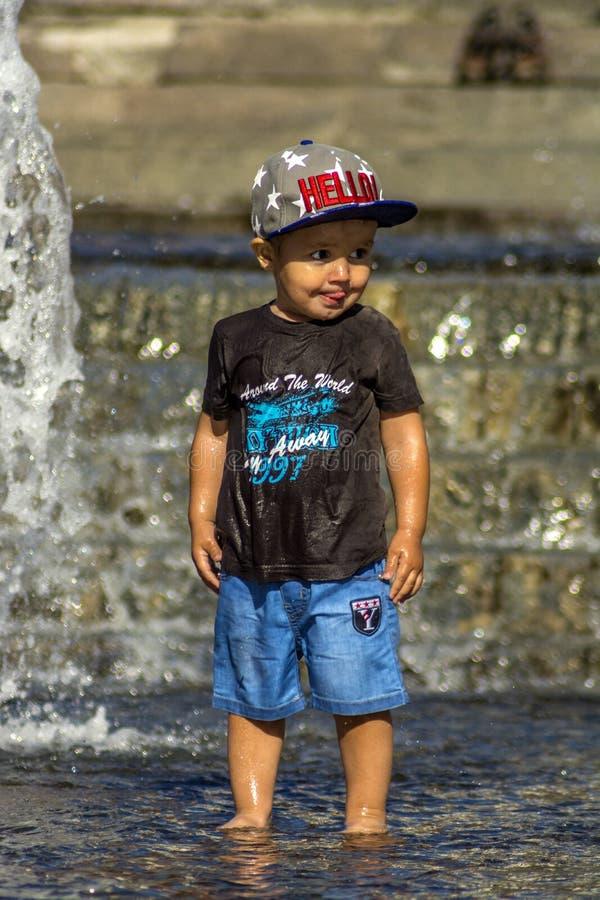 Kiev, Ukraine, le 7 août 2018 Le garçon s'échappe de la chaleur dans la fontaine de ville images stock