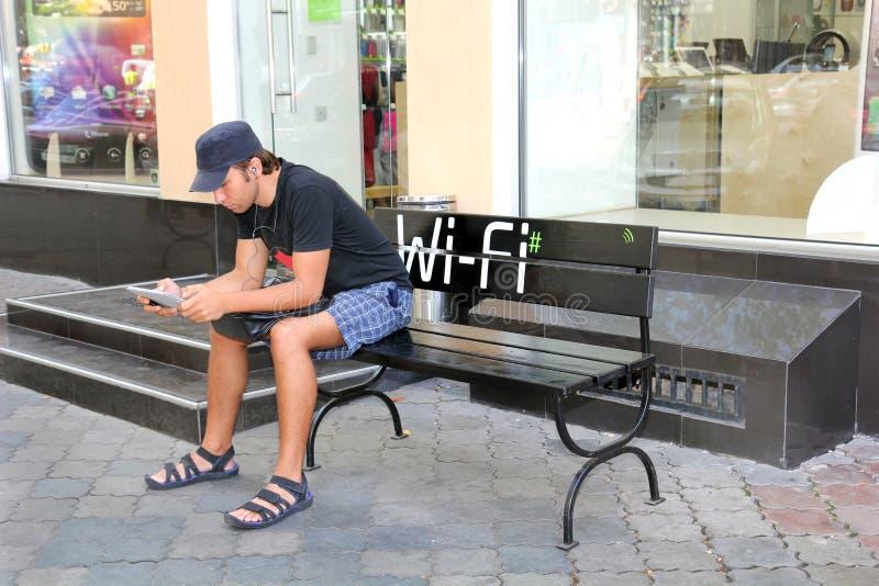 Kiev, Ukraine, 16 09 le jeune homme 2011 dans des écouteurs s'assied sur un banc avec un instrument photographie stock libre de droits