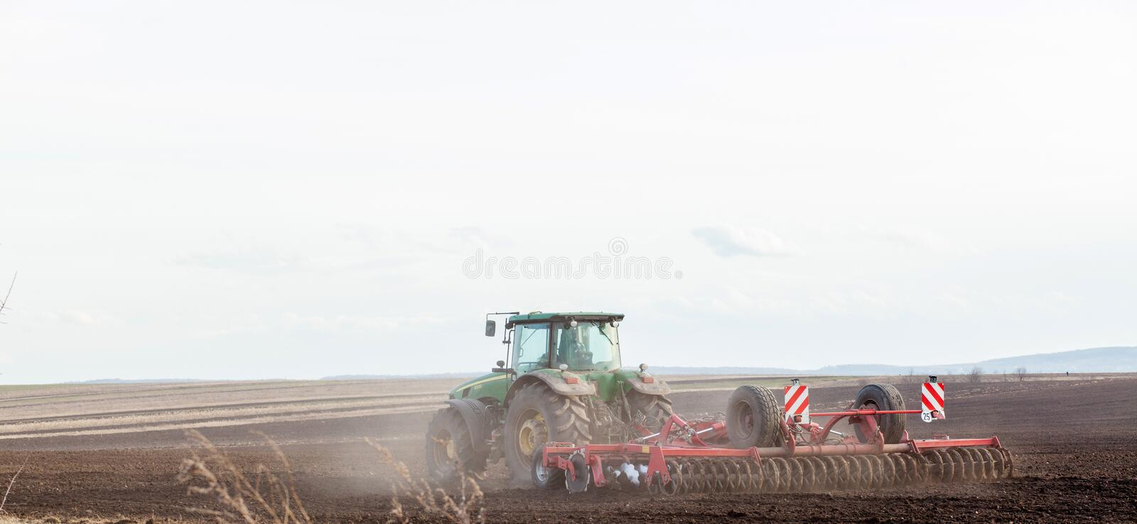KIEV, UKRAINE - MARCH 27, 2019: Agriculture,tractor preparing land with seedbed cultivator as part of pre seeding activities in royalty free stock photos