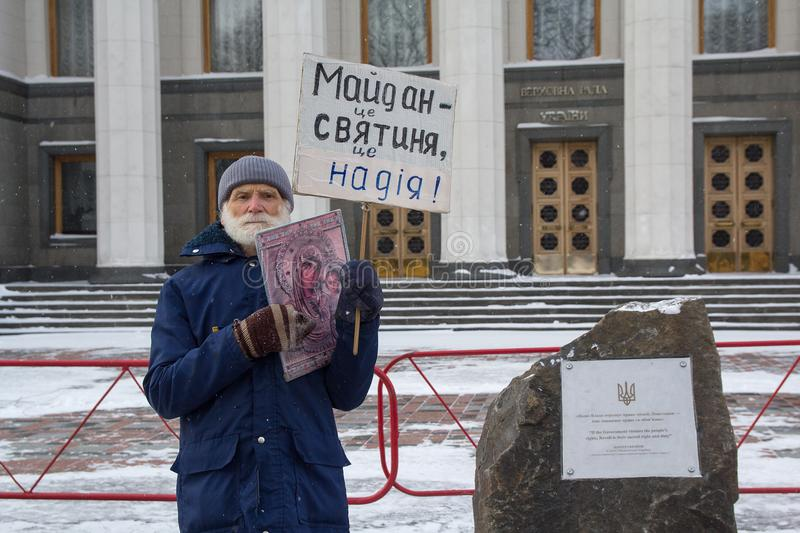 Kiev, Ukraine - March 04, 2018: An elderly man in a solitary picket near the High Rada with an icon and a poster royalty free stock images
