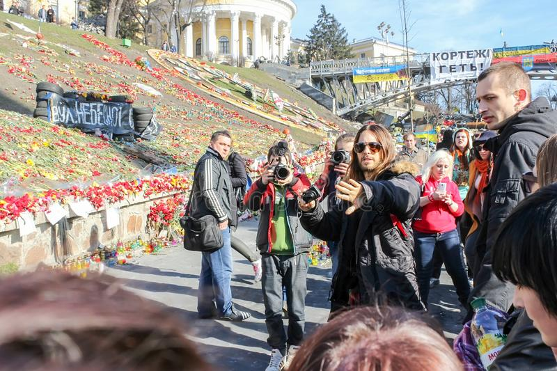 Jared Leto surrounded by a crowd of Ukrainian fans taking pictures near the hill with laid flowers royalty free stock photos
