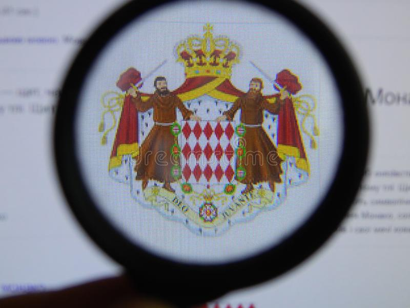 KIEV, UKRAINE - MARCH 23, 2019: Monaco coat of arms viewed through a magnifying glass royalty free illustration