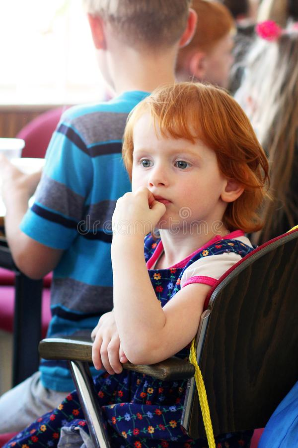 Kiev, Ukraine - March 3, 2018: A very beautiful little red-haired girl is sitting at a table and looking into the distance stock image