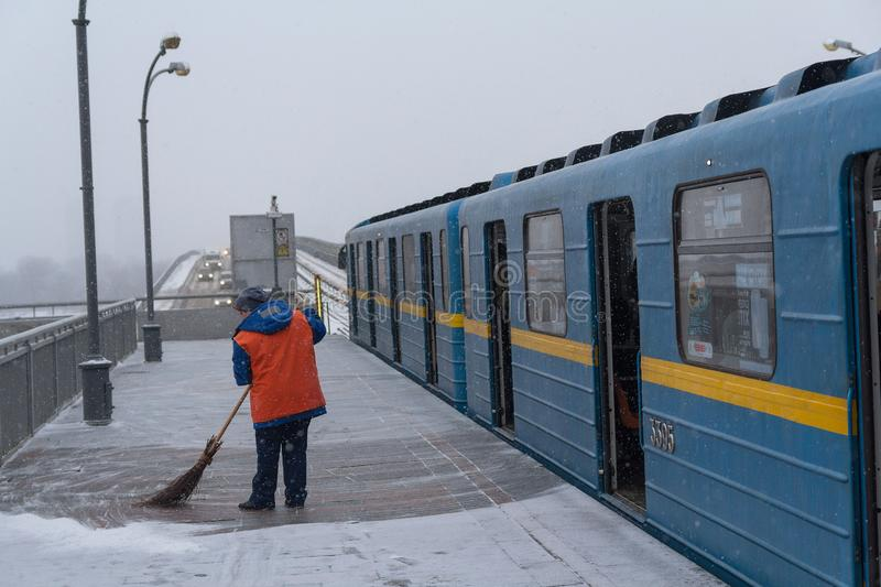 Kiev, Ukraine - March 02, 2018: Woman in a yellow vest cleans the snow on a subway platform stock photography