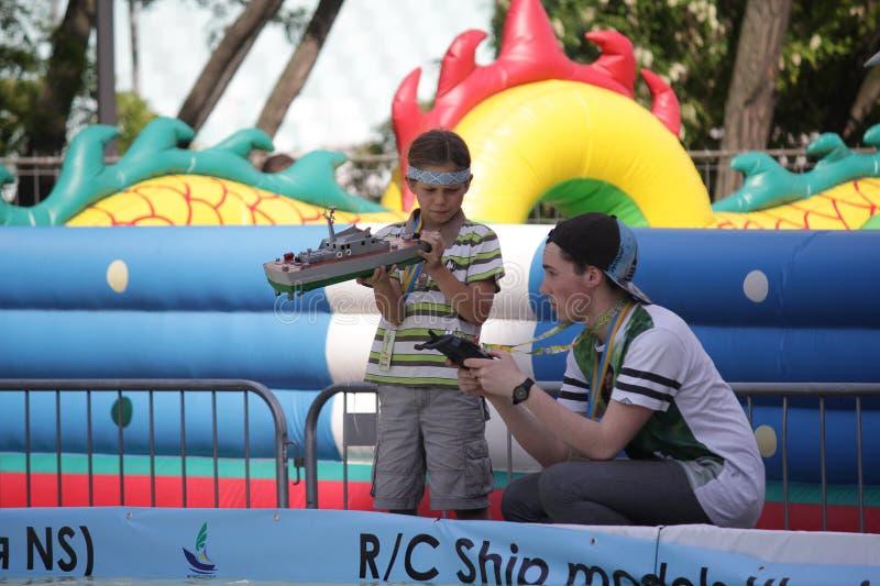 Kiev, Ukraine - May 05, 2016: Boys are preparing to launch a ship model royalty free stock photo
