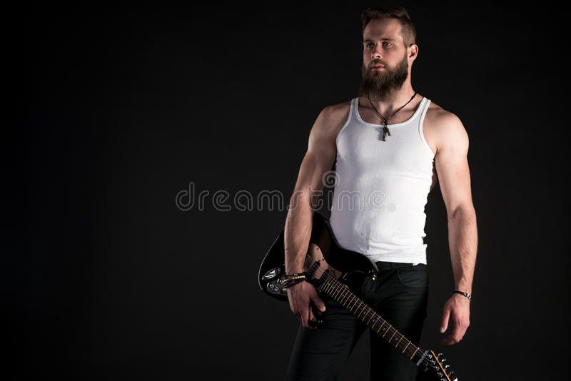 KIEV, UKRAINE - May 03, 2017. A charismatic and stylish man with a beard holds an electric guitar in his hand on a black isolated royalty free stock photography