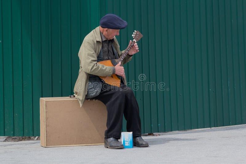 Kiev, Ukraine - May 03, 206: An elderly man makes a living play stock image