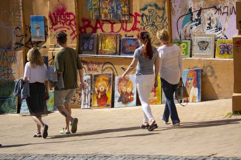 Kiev, Ukraine - May 19, 2019: People pass near paintings sold by artists on Andrew Descent royalty free stock photo
