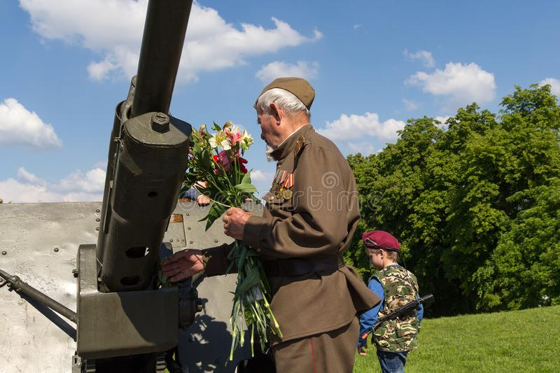 Kiev, Ukraine - May 09, 2016: Veteran lays flowers at the gun. In the Park of Eternal Glory stock photography