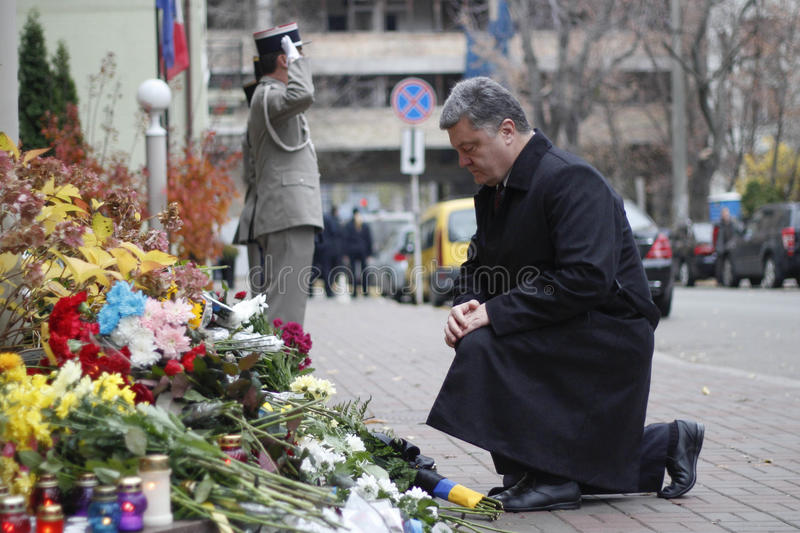 KIEV,UKRAINE - November 14, 2015: People lay flowers at the French Embassy in Kiev in memory of the victims terror attacks in Pari. People lay flowers at the royalty free stock image