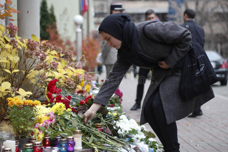 KIEV,UKRAINE - November 14, 2015: People lay flowers at the French Embassy in Kiev in memory of the victims terror attacks in Pari. People lay flowers at the royalty free stock photos