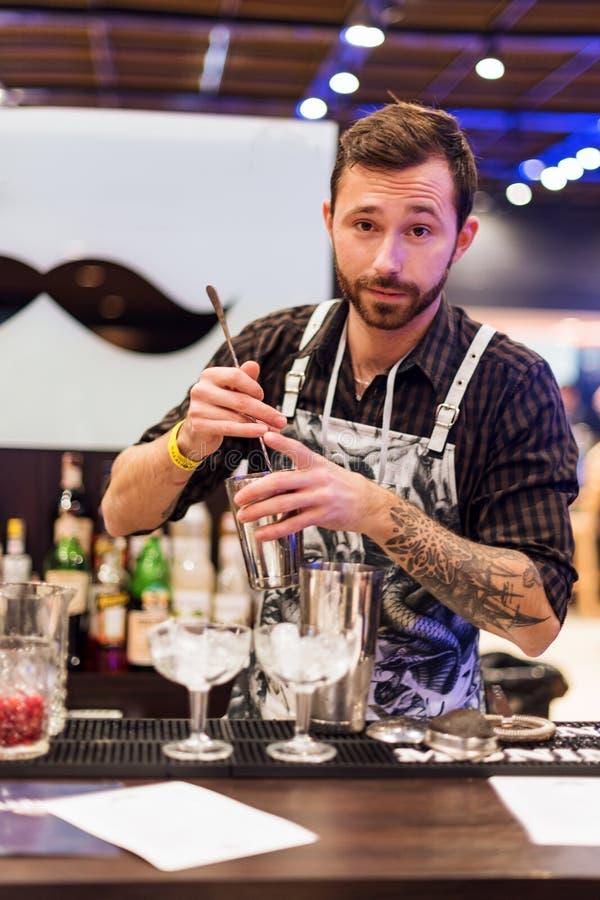 KIEV, UKRAINE - 30 OCTOBER, 2016: Barman festival. Young handsome bartender is making cocktail. royalty free stock photo