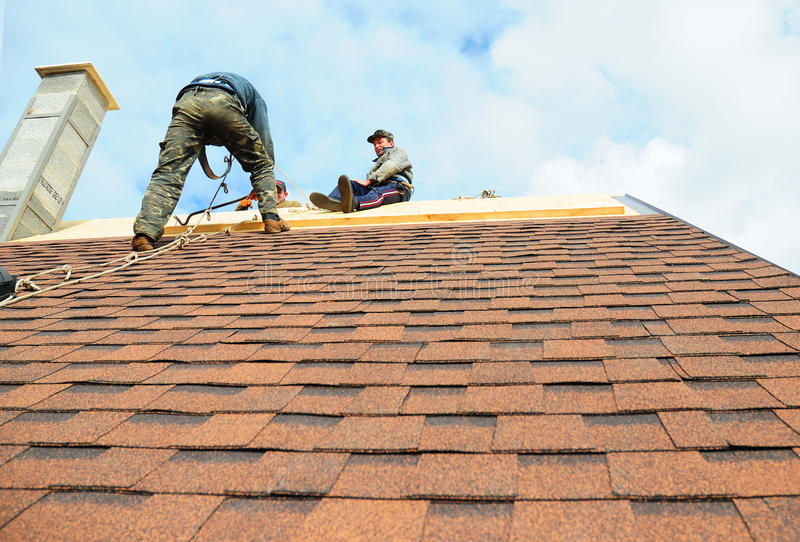 KIEV - UKRAINE, OCTOBER - 18, 2016: Roofing Contractors Install New House Roofing with Asphalt Shingles. royalty free stock image