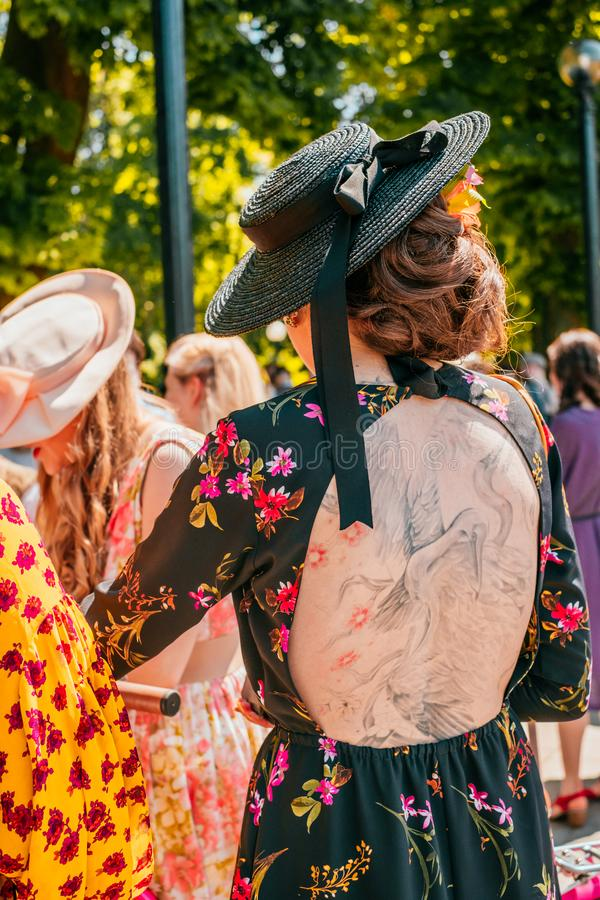Kiev Ukraine Retro Cruise May 2019. Kiev, Ukraine - May 19, 2019: Girl with a tattoo on the back in black floral printed vintage dress participating in bicycle stock photo