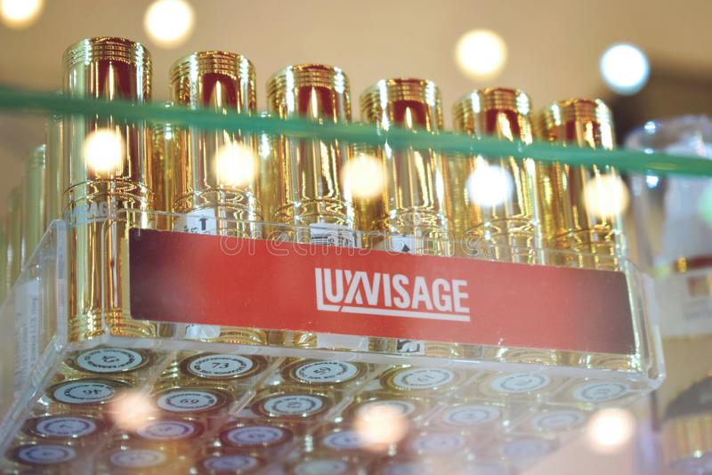 Kiev, Ukraine 19 September, 2018: Belarusian cosmetics Luxvisage lipstick in gold cases. A lot of lipstick on a glass shelf in. The store, many, shop, sale royalty free stock images