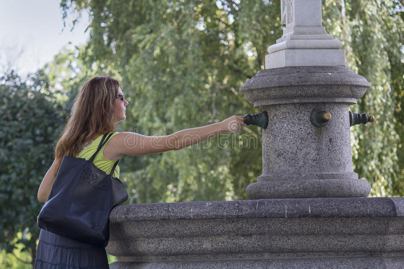 Kiev, Ukraine - September 09, 2015: Woman apply a coin for good luck to the fountain-magnet. On the territory of St. Michael`s Cathedral royalty free stock image