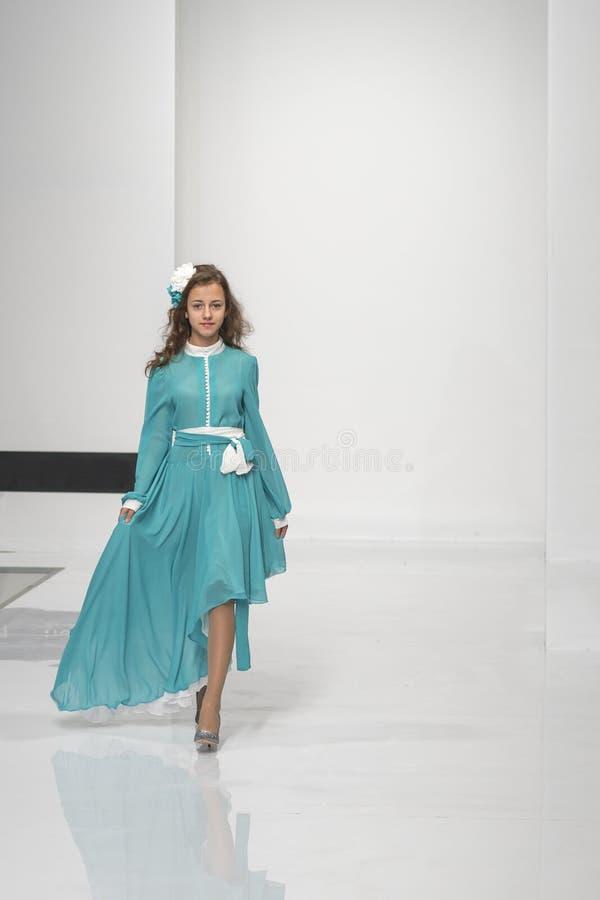 Kiev, Ukraine 7 septembre 2018 le mannequin dans une robe bleue marche sur une étape blanche Photo verticale image libre de droits