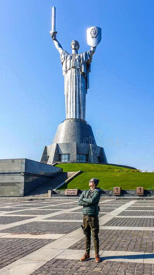 Kyiv - A young man standing under the motherland monument. KIev/Ukraine-04222019: A young man standing under the Mother Motherland Monument, with his arms royalty free stock images
