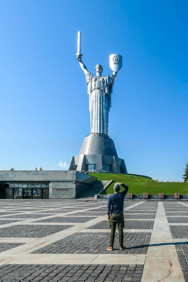 Kyiv - A young man standing under the motherland monument. KIev/Ukraine-04222019: A young man standing under the Mother Motherland Monument, looking t the stock photo