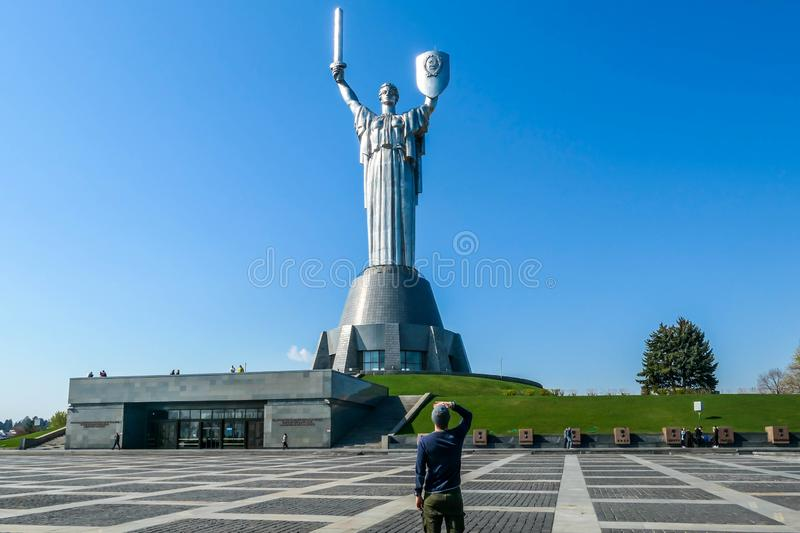 Kyiv - A young man standing under the motherland monument. KIev/Ukraine-04222019: A young man standing under the Mother Motherland Monument, looking t the stock photos