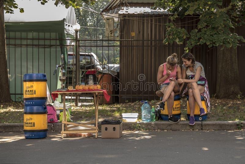 KIEW, UKRAINE - 9. AUGUST 2015: Junge Mädchen, die Kwaß ein populäres Ost - europäisches Getränk überprüft ihren Smartphone auf e stockfotografie