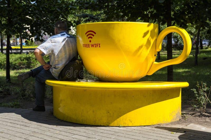Kiew, Ukraine - 9. August 2017: Mann sitzt auf einer Bank nahe dem stilisierten Punkt der Verteilung des wifi lizenzfreie stockfotos