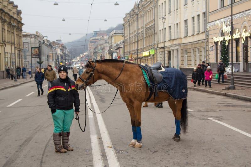 Kiew, Ukraine - 28. Dezember 2017: Mädchen lädt Stadtbewohner fegt auf einem Pferd ein stockfoto