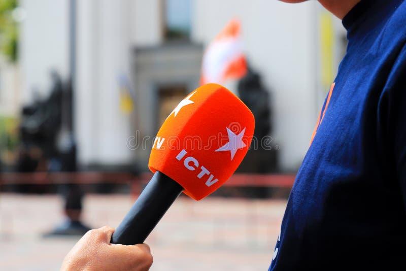 Kiew, Ukraine, 28 06 2019 Ein Mann hält ein rotes Mikrofon mit dem Logo des berühmten populären ukrainischen Fernsehkanals ICTV stockfotos