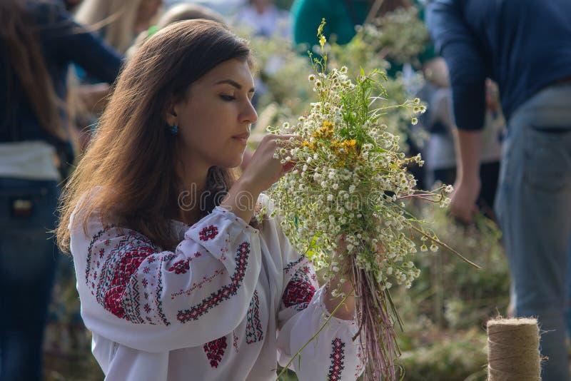 Kiew, Ukraine - 6. Juli 2017: Mädchen windt einen Kranz von Kräutern und von Blumen am Festival lizenzfreie stockfotos