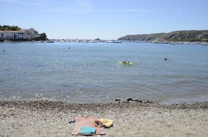 Kiezelachtige handdoek en zak bij de kust stock foto