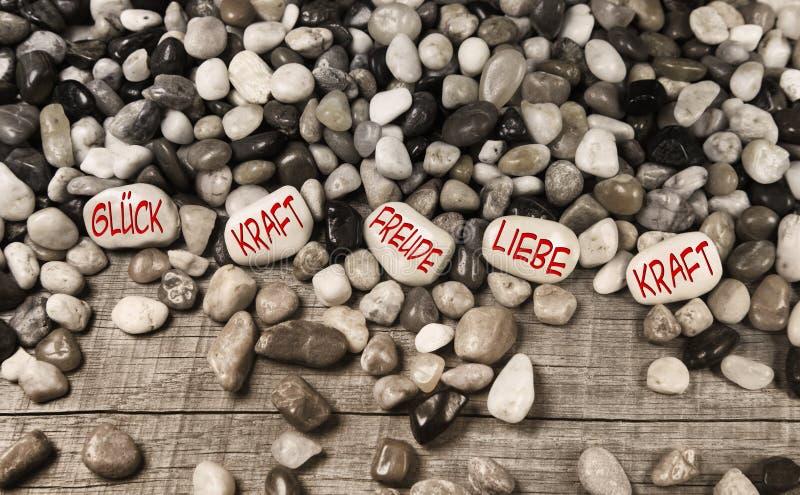 Kiezelsteenstenen met Duitse teksten voor geluk, kracht, pret, liefde en po royalty-vrije stock foto