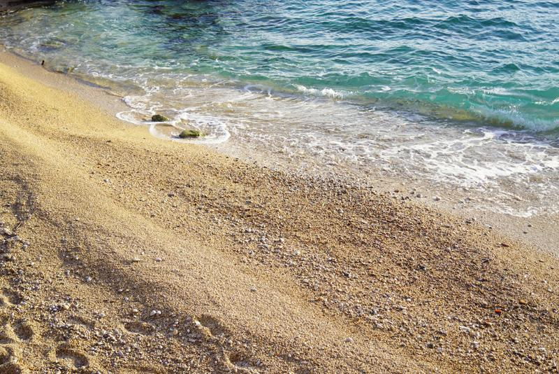 Kiezelsteenstrand, door duidelijke blauwe wateren wordt gewassen dat stock fotografie