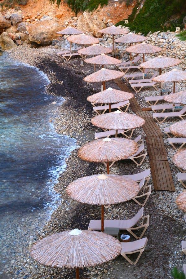 Kiezelsteenstrand met een lijn van rieten paraplu's stock foto's