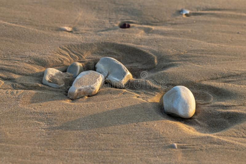 Kiezelstenen in het zand bij schemeringzonsondergang stock fotografie