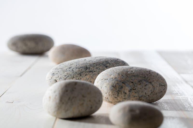 Kiezelstenen op witte houten achtergrond voor mindfulness of yoga worden geplaatst die stock afbeeldingen