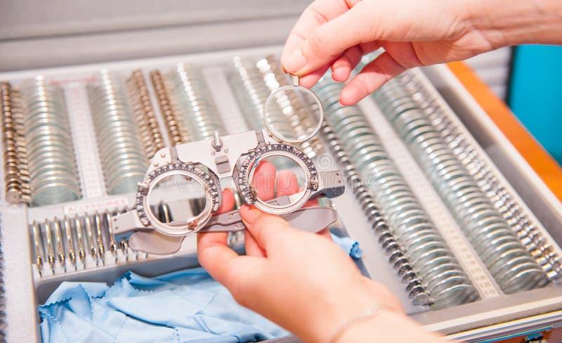 Kiezen de opticien vrouwelijke handen lenzen van reeks van correctieve lens die op de platen van de vorm wijzen op: concaaf, conv stock foto's
