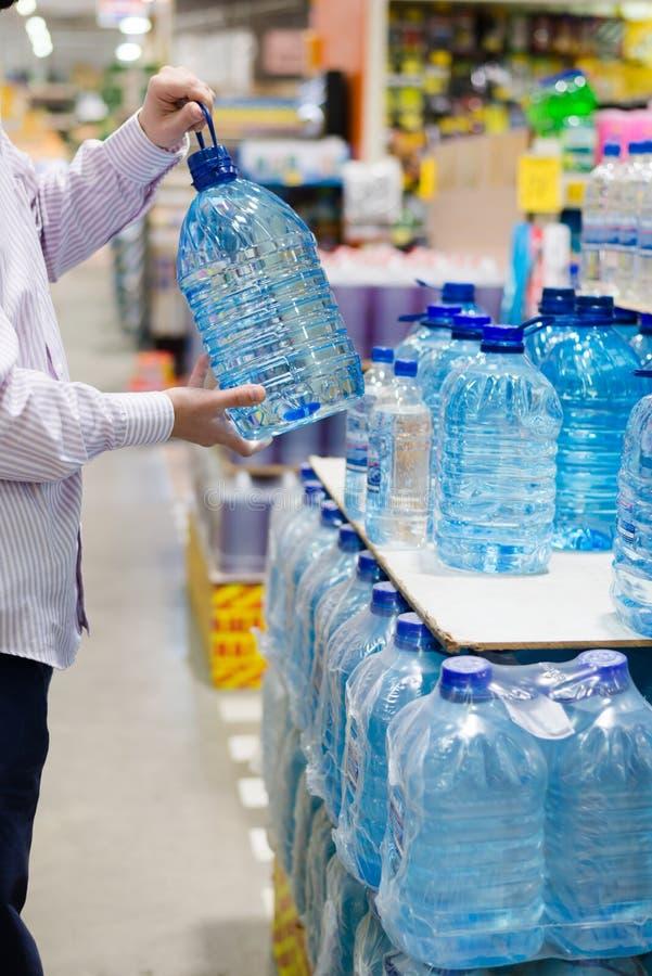 Kiezend, selecterend of kopend een fles mineraal drinkend of distillerend water bij de het winkelen opslagnadruk op handen stock fotografie
