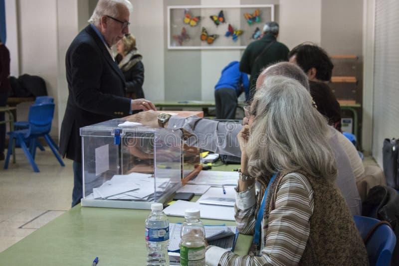 Kiezer die envelop binnen urn introduceren bij kiesuniversiteit voor Spaanse algemene verkiezingen in Madrid, Spanje royalty-vrije stock foto's