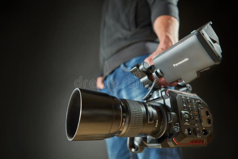 Kijów Ukraina, Kwiecień, - 22, 2018: Kamera wideo mężczyzna odizolowywający z film kamerą Panasonic AU-EVA1 w studiu obraz stock