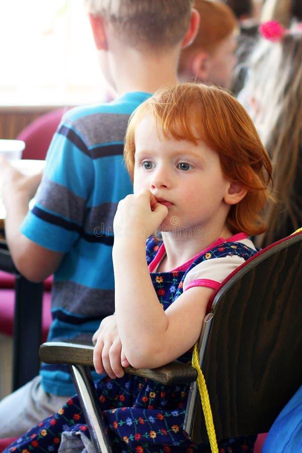 Kijów Ukraina, Marzec, - 3, 2018: Bardzo piękna mała miedzianowłosa dziewczyna jest siedząca przy stołem i patrzeć w odleg obraz stock