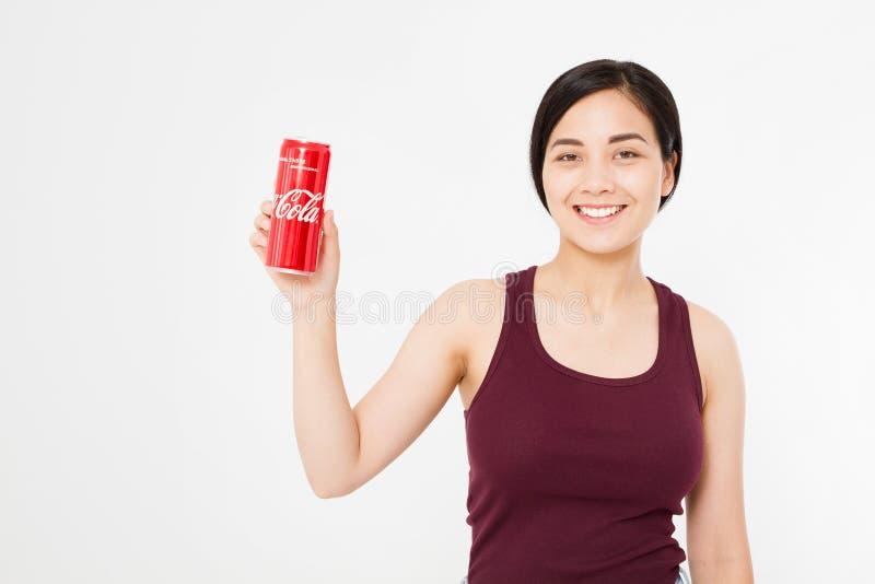 KIJÓW, UKRAINA - 06 28 2018: Szczęśliwy azjata, koreańska kobieta, dziewczyny mienia koka-kola słój słodka woda Illustrative arty fotografia stock