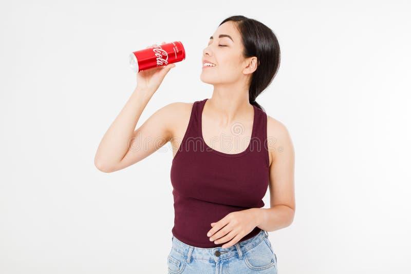 KIJÓW, UKRAINA - 06 28 2018: Szczęśliwy azjata, koreańska seksowna kobieta pije koka-kola słój słodka woda Illustrative artykuł w zdjęcia royalty free