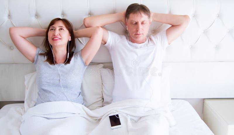 Kijów, Ukraine-09 10 2018: jabłczani earpods Szczęśliwa W średnim wieku para relaksuje na łóżku w domu i patrzeje kamerę i słucha fotografia stock