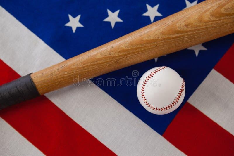 Kij bejsbolowy i piłka na flaga amerykańskiej zdjęcia stock