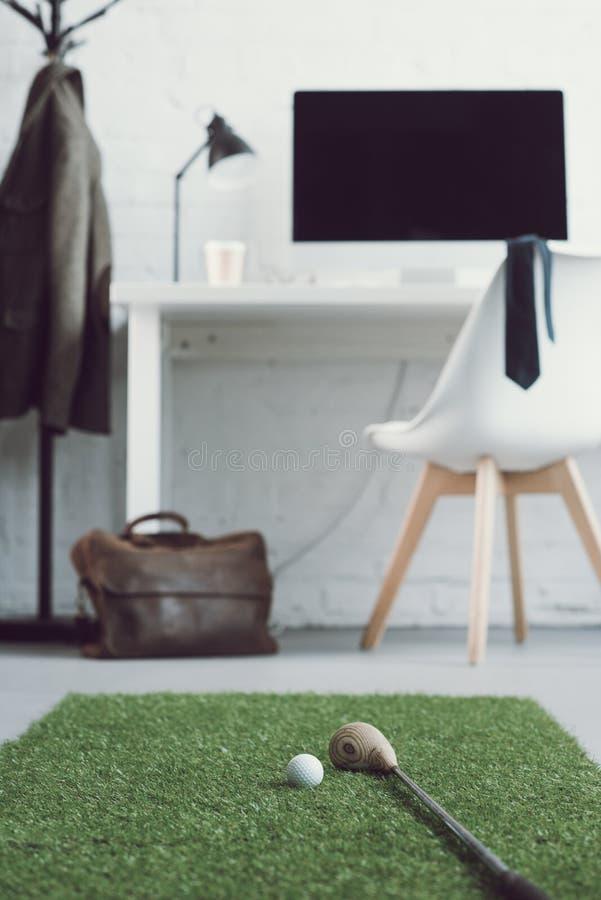 kij golfowy i piłka na zielonej trawy dywanie w nowożytnym miejscu pracy fotografia stock