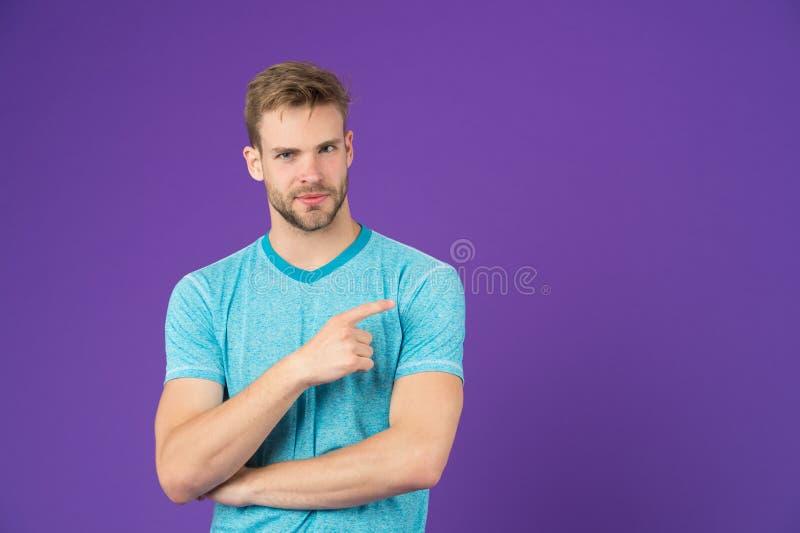 Kijk hier Mensen spier knappe ongeschoren kerel op violette achtergrond die de ruimte van het vingerexemplaar richten Mannelijkhe stock afbeeldingen