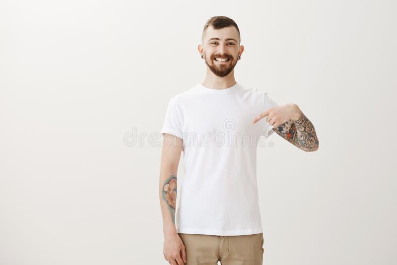 Kijk hoe schoon mijn t-shirt Portret die van tevreden knap tevreden mannetje met baard en tattos, op borst richten en stock foto's