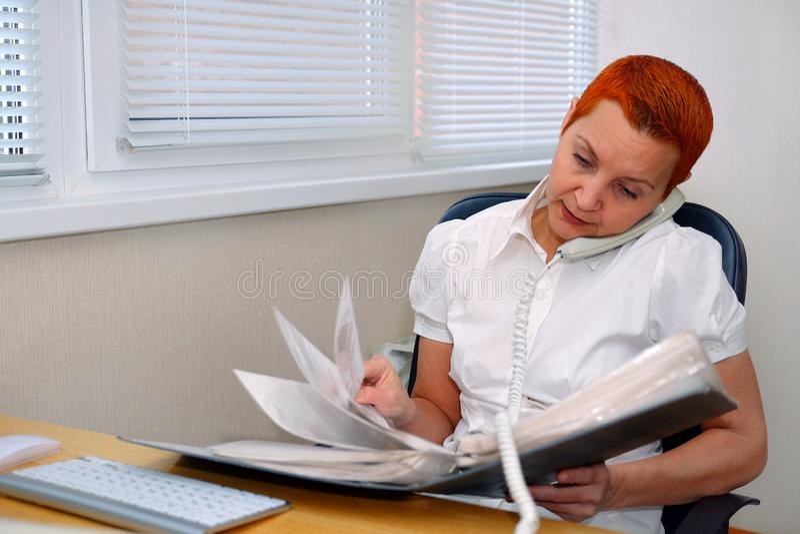 Kijkend door de documenten, de Manager die van het meisjesbureau op de telefoon spreken royalty-vrije stock foto